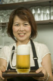 Woman serving ice cold beer Stock Image