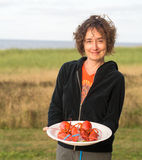 Woman serving lobster at beach Stock Photos