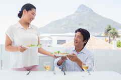 Woman serving a meal for her boyfriend Royalty Free Stock Image