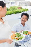 Woman serving a meal for her boyfriend Stock Photos