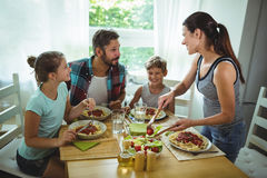 Woman serving meal to her family. At home stock photography