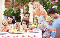Woman Serving Meal To Two Families. Ouside stock image