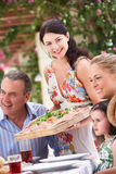 Woman Serving At Multi Generation Family Meal. Outside Stock Images