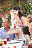 Woman Serving At Multi Generation Family Meal. Outside Laughing Stock Images