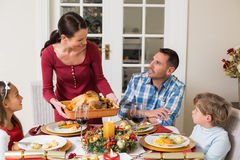 Woman serving roast turkey to her family Royalty Free Stock Images