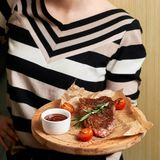 Woman serving steak on round wooden plate Royalty Free Stock Photo