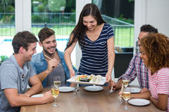Woman serving sushi to friends while drinking wine Stock Photo