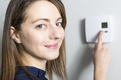 Woman set the thermostat at home Stock Photos