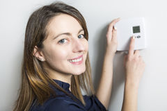 Woman set the thermostat at home. A woman set the thermostat at home Royalty Free Stock Images