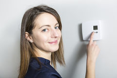 Woman set the thermostat at home. A woman set the thermostat at home Royalty Free Stock Photos