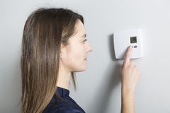 Woman set the thermostat at home. A woman set the thermostat at home Stock Photography