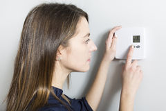 Woman set the thermostat at home. A woman set the thermostat at home Stock Photos