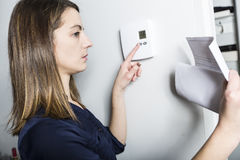 Woman set the thermostat at home. A woman set the thermostat at home Stock Photo