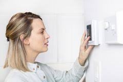 Woman set the thermostat at house. A woman set the thermostat at house Royalty Free Stock Photos