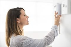 A woman set the thermostat at house. Woman set the thermostat at house stock photos
