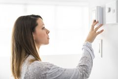 A woman set the thermostat at house. Woman set the thermostat at house royalty free stock images