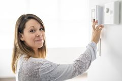 A woman set the thermostat at house. Woman set the thermostat at house royalty free stock photography