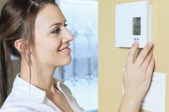 Woman set the thermostat at house Stock Image