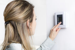 Woman set the thermostat at house. A woman set the thermostat at house Stock Photography