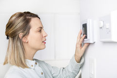 Woman set the thermostat at house. A woman set the thermostat at house Royalty Free Stock Image
