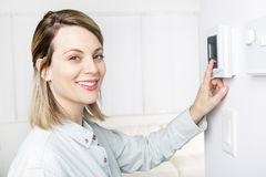 Woman set the thermostat at house. A woman set the thermostat at house Stock Images