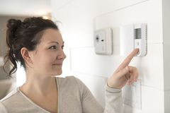 A nice woman set the thermostat at house. A woman set the thermostat at house stock image