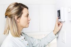 Woman set the thermostat at house. A woman set the thermostat at house Royalty Free Stock Photo