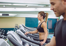 Woman setting control panel of treadmill for training Stock Image