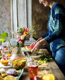 Woman setting fruits and drinks table for party Royalty Free Stock Images