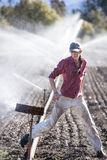 Woman setting irragation sprinklers. Stock Photos