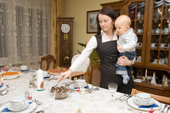 Woman setting table with her child Royalty Free Stock Images