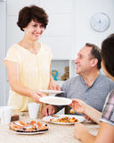 Woman setting table for lunch. Cheerful mature women setting table for family lunch at home indoors. Focus on man Stock Photo