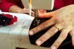 Woman sewing, closeup of hands. Close-up of hands  woman sewing black pants Stock Photo