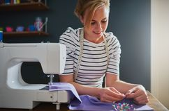 Woman sewing clothes stock image