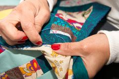 Woman sewing for finish a quilt. Royalty Free Stock Photo