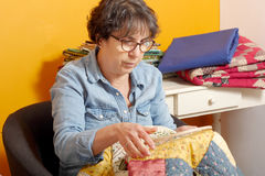 Woman sewing for finish a quilt. Seamstress woman sewing for finish a quilt Stock Photography