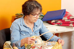 Woman sewing for finish a quilt. Royalty Free Stock Image