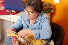 Woman sewing for finish a quilt. Seamstress woman sewing for finish a quilt Stock Photo