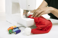 Woman sewing a hat for Santa Claus. On the sewing machine Stock Image