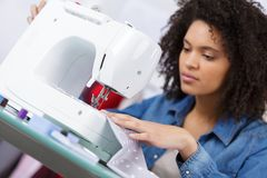 Woman sewing at working place in fashion workshop Stock Photo