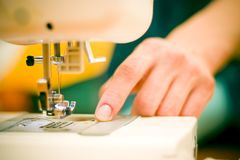 Woman at sewing machine. royalty free stock photography