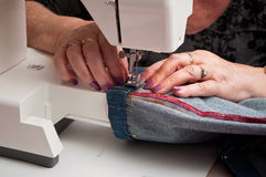 Woman with a sewing machine and blue jeans hem Royalty Free Stock Photography