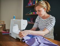 Woman sewing on sewing machine stock images