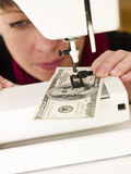 Woman sewing money Stock Images