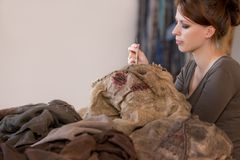 Woman is sewing a scarecrow mask and costume. For carneval or halloween, maybe a prop for a movie or theatre stock image