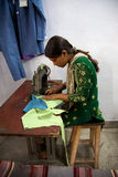 Woman sewing several pieces of clothes in Agra for Pushpanjali Stock Images