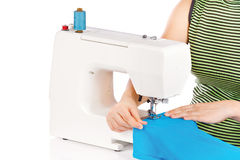 Woman is sewing on the sewing machine Stock Photos