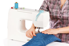 Woman is sewing on the sewing machine Stock Photo