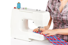 Woman is sewing on the sewing machine Royalty Free Stock Image