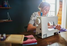 Woman sewing on sewing machine stock photo